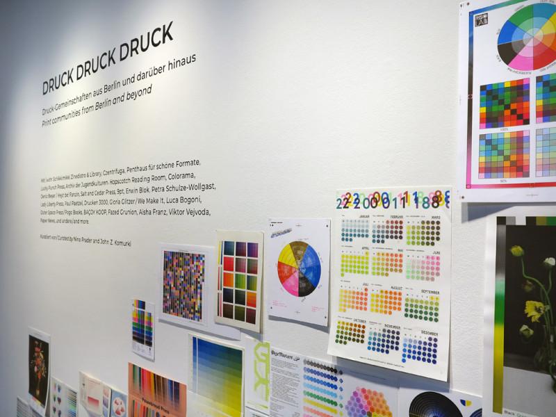 Wandtext der Ausstellung und verschiedene Blätter mit Darstellungen von Farbpaletten.