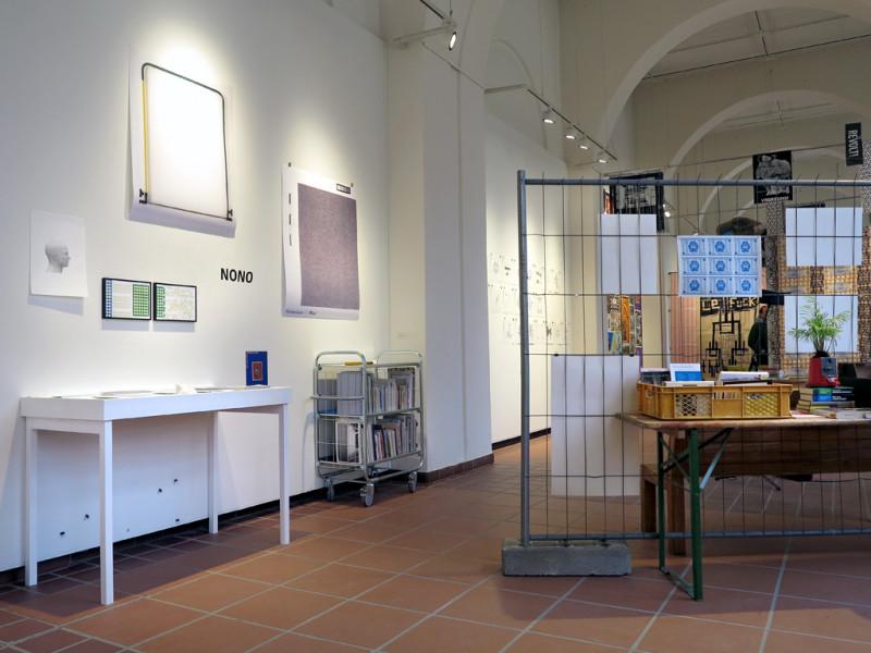 Mehrere schlichte Drucke hängen an der Wand. Davor ist die Bibliothek auf einer Vitrine und in einem Regal auf Rollen präsentiert.