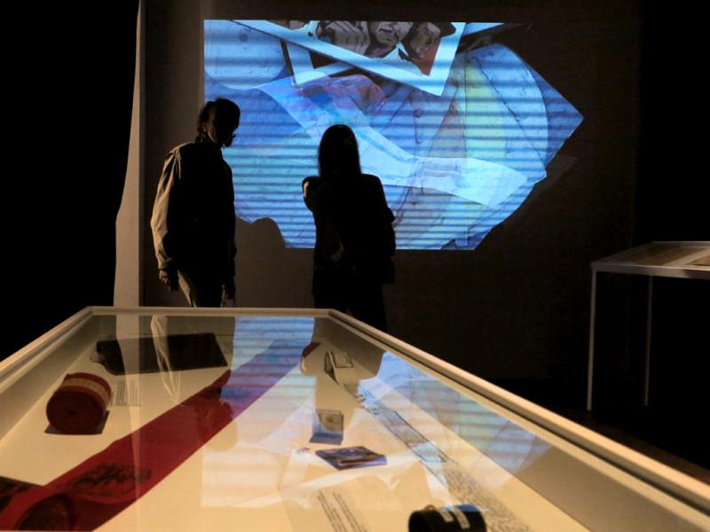 Im Vordergrund eine Glasvitrine  mit verschiedenen Gegenständen. Im Hintergrund stehen zwei Peronen vor einer Projektion,die digitalisierte Scans von Zines zeigt.