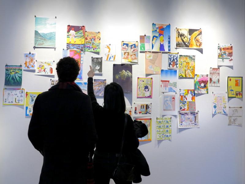 Vor einer weißen Wand mit verschiedenen bunten Drucken stehen, von hinten fotografiert,  ein Mann und eine Frau.