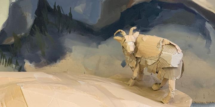 Ein Schaf aus Pappe steht auf einem Felsen aus Pappmaché.