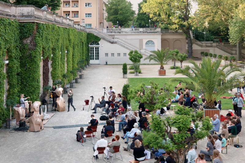 viele Menschen sitzen auf der Terrasse bei der Eröffnung der Ausstellung