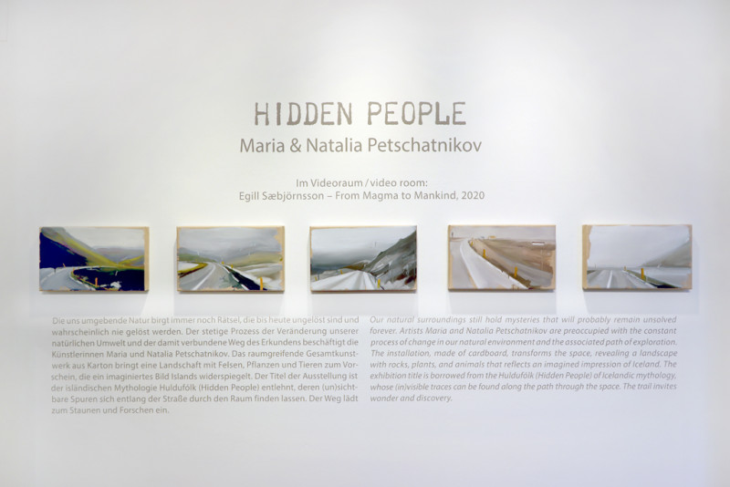 fünf Bilder hängen an der Wand, auf denen eine Straße zu sehen ist. Um die Bilder herum steht der Wandtext zur Ausstellung