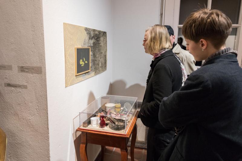 Besucherinnen betrachten eine Blumenzeichnung, deren Rahmen auf einer Tapete befestigt ist. Darunter steht ein kleiner Tisch mit unterschiedlichen Gegenständen.