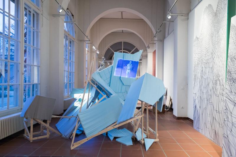 Mitten im Galerieraum ist ein raumgreifendes Gerüst, das aus Holzbalken und darauf befestigten Platten besteht. Auf die blauen Platten wird ein Video projiziert.