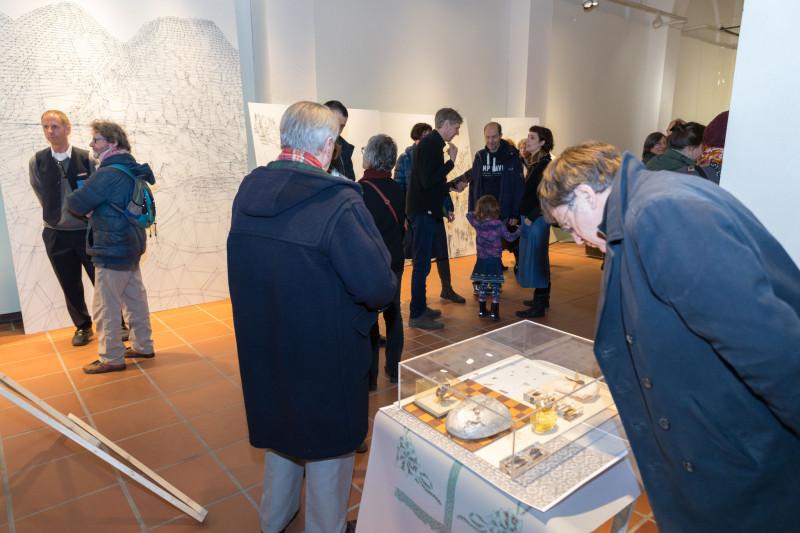 Besucher:innen der Ausstellung betrachten die Arbeiten oder unterhalten sich.