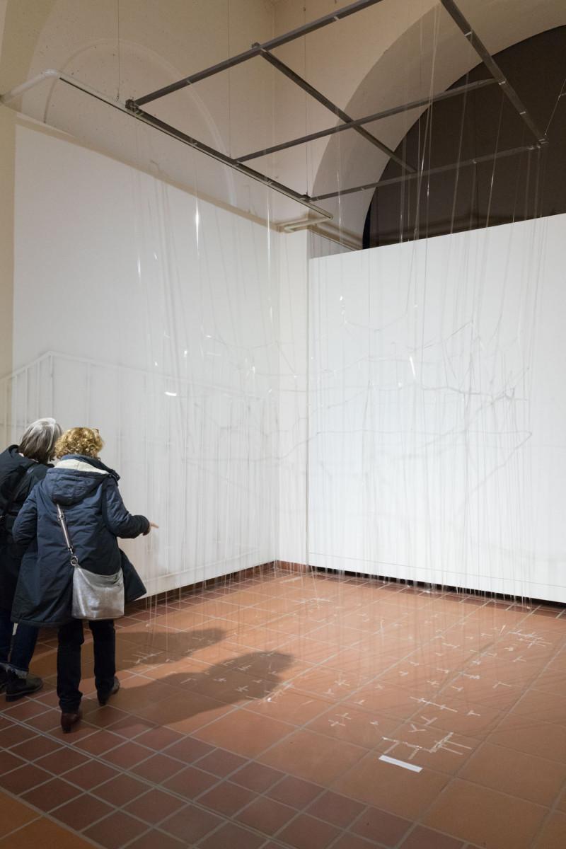 Den Galerieraum nimmt eine überlebensgroße Struktur aus durchsichtigen Klebestreifen ein. Zwei Betrachtende stehen davor.