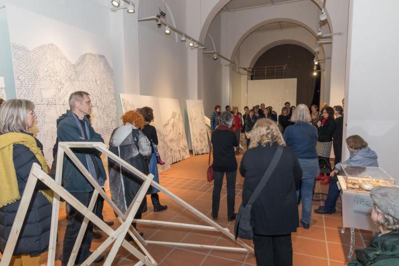 Im Galerieraum stehen viele Besucher:innen während gerade eine Eröffnungsrede gehalten wird.