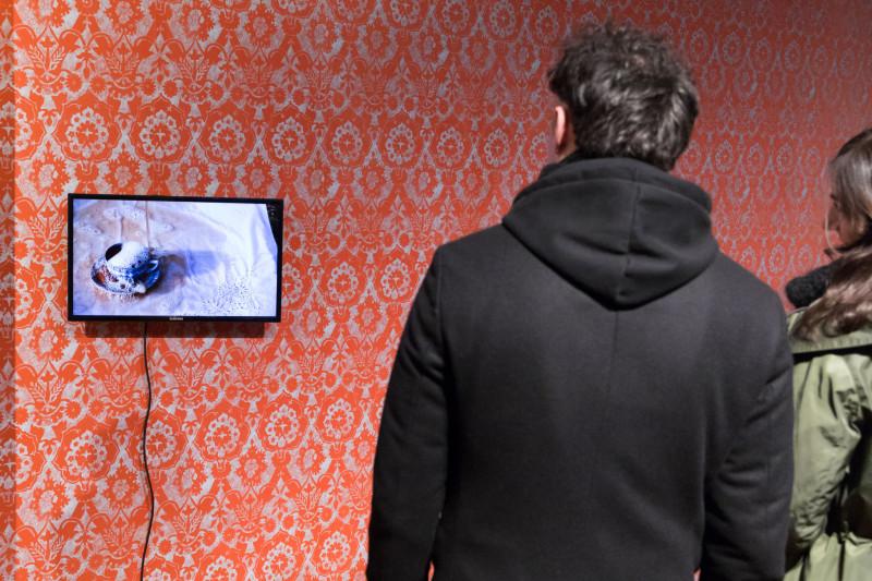 Zwei Besucher:innen betrachten ein Video in der Ausstellung.