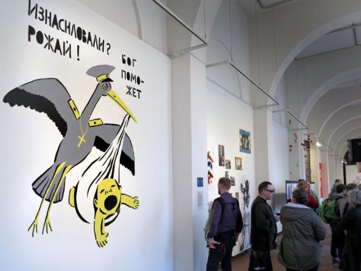Post-Soviet Cassandras, Ausstellungseröffnung. Vorn: Wandmalerei von Gandhi. Ein grauer Storch, dessen Federkleid wie eine Uniform aussieht und der eine Kette mit einem Kreuz um den Hals trägt, hält ein schreiendes Baby in einem Tuch. Drüber steht: Vergewaltigt worden? Gebäre! Gott wird schon helfen.