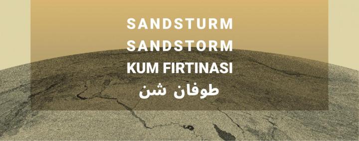Vor einem Sandhügel liegt ein sandfarbenes Feld in welchem auf drei Sprachen Standsturm geschrieben steht