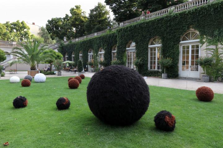 Mit Fell überzogene Bälle liegen auf der Wiese vor der Galerie im Körnerpark