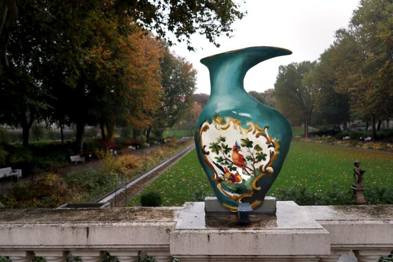 Eine Vase aus Pappe in grünem Ton und einem Vogelmotiv auf der Balustrade mit Blick in den Körnerpark im Hintergrund