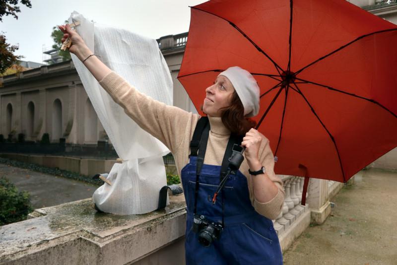 Man sieht eine Frau mit rotem Regenschirm die ein weiß verpacktes Kunstwerk entpackt