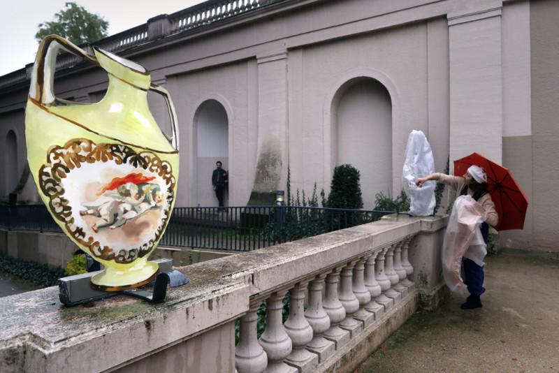 Im Vordergrund eine Blumenvase auf der Balustrade und im Hintergrund die Künstlerin beim Entpacken einer weiteren Arbeit