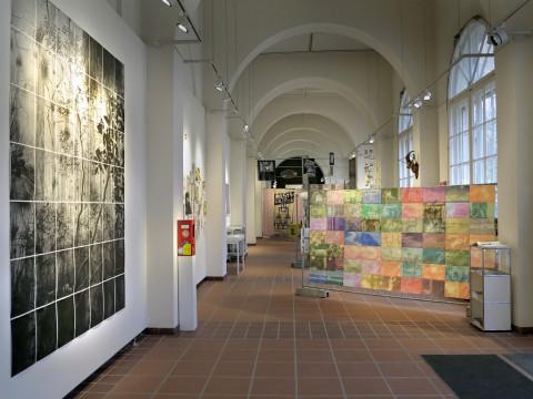 Links an der Wand ein Raster aus Bilder in Schwarz Weiß, in der Mitte farbige Drucke auf einem Bauzaum aufgehängt