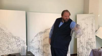 Ein Mann steht vor drei Leinwänden und holt etwas aus einer Plastiktüte
