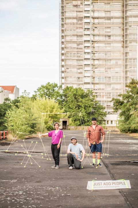 Drei Personen stehen vor einen Hochhaus und haben verschiedene Stäbe in der Hand