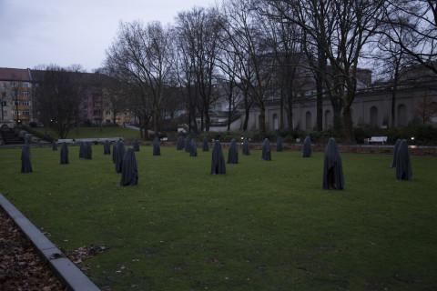 28 in dunkle Tücher verhüllte Frauen stehen auf der Wiese im Körnerpark